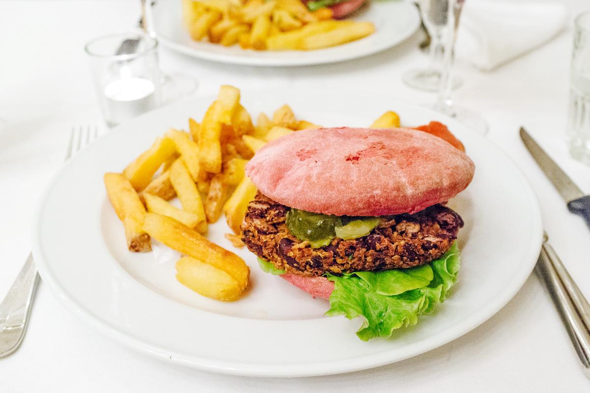 Burger de quinoa et de haricots rouges dans un petit pain aux betteraves rouges, oignons frits, chips d'aneth et salsa verde
