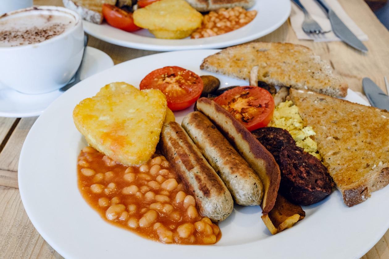 Repas végétalien au Green Kitchen Vegan Cafe à Brighton: Full English Breakfast avec du tofu brouillé, deux saucisses végétale, du bacon végétal, deux morceaux de black pudding, des haricots blancs à la sauce tomate et des tomates rôties, des croquettes de pommes de terre et du pain grillé