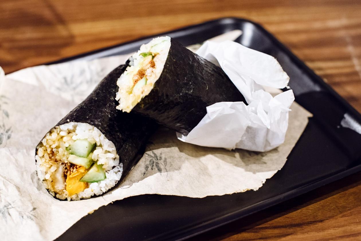 Repas végétalien chez Happy Maki, à Brighton en Angleterre. Rouleau de riz vinaigré enveloppé d'une feuille de nori et farci avec des légumes et des protéines de soja grillées.