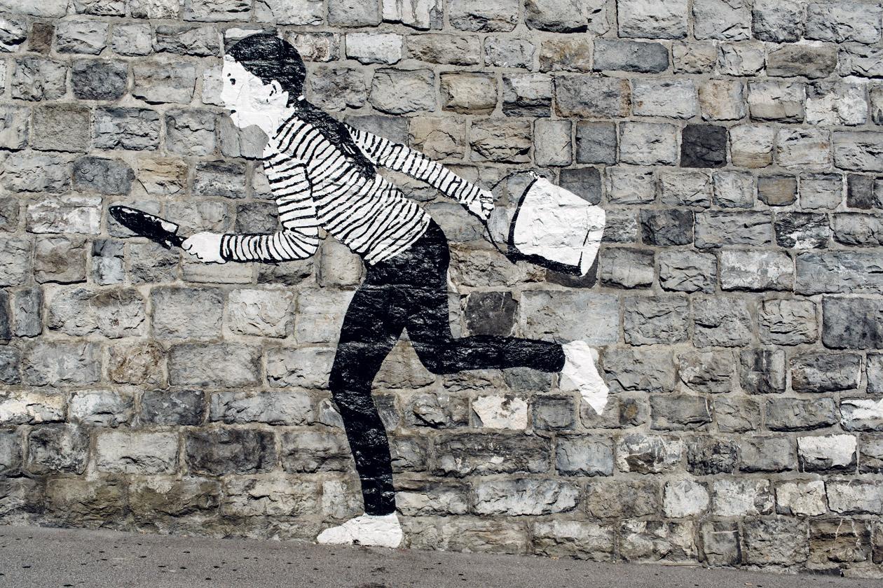 Lausanne Jardins 2019 –Place to Live – Un enfant peint sur les murs de Lausanne prend soin des plantes qui poussent de manière autonomes entre les pierres