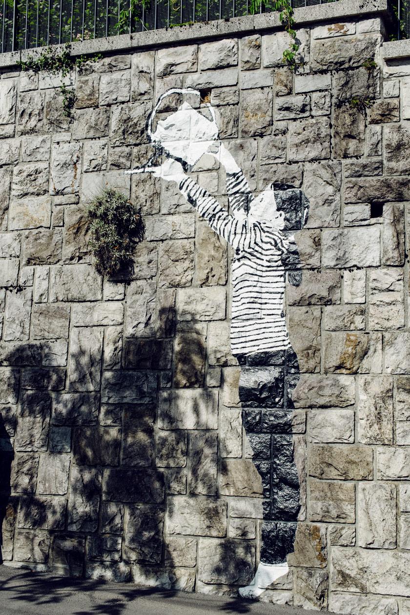 Lausanne Jardins 2019 – Place to Live – Un enfant peint sur les murs de Lausanne prend soin des plantes qui poussent de manière autonomes entre les pierres