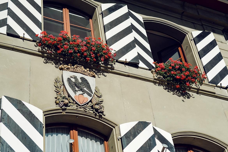 Façade de l'Hôtel de Ville d'Aarberg, avec le blason de la commune et des géraniums rouges aux fenêtres