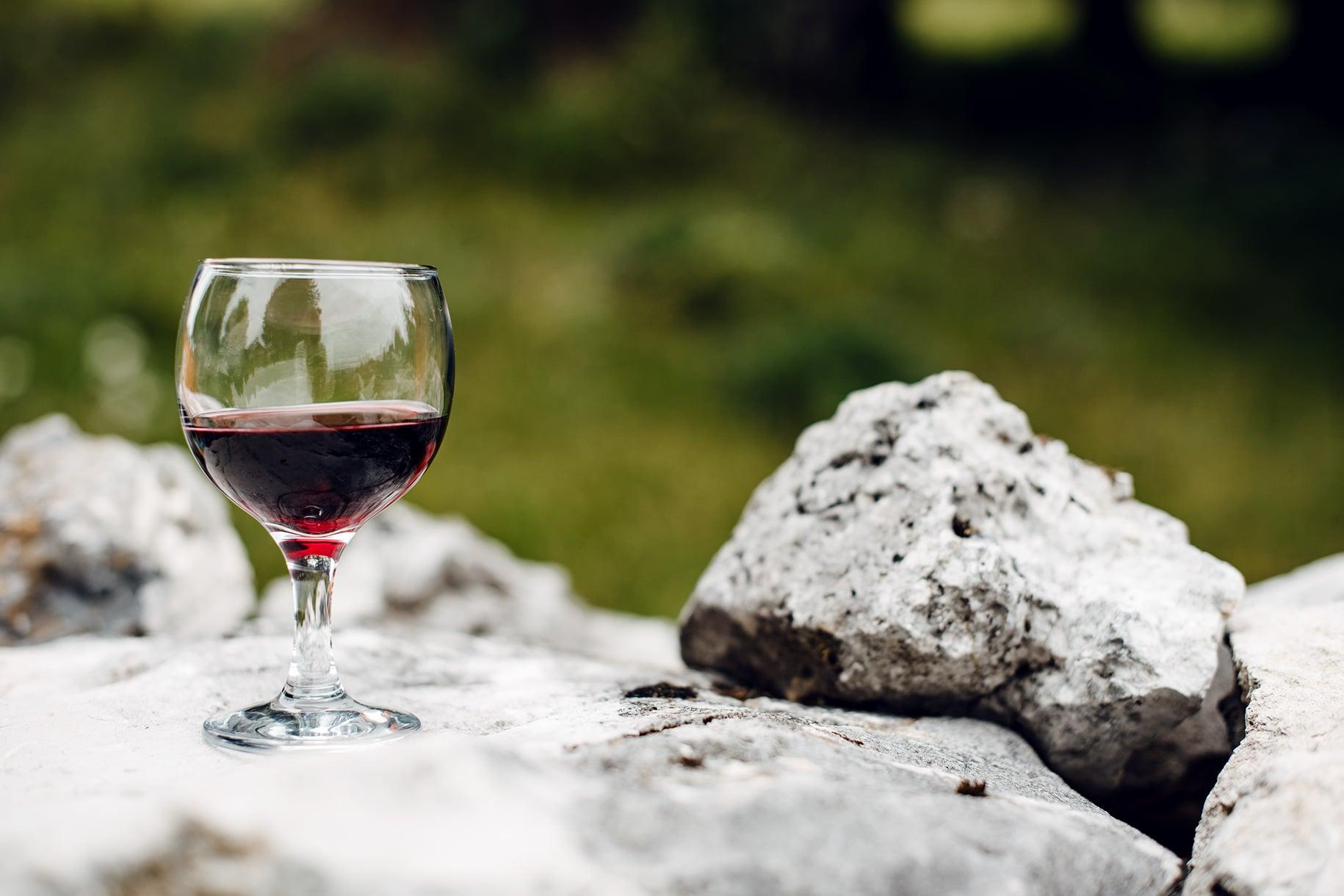 Verre de vin rouge posé sur un muret en pierres