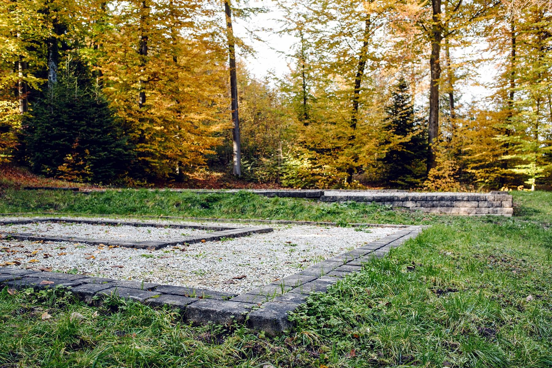 Emplacement de deux bâtiments de l'ancien sanctuaire romain, marqué par des grandes zones de gravier entourées de murets bas en pierres – Promenade automnale dans la forêt de Petinesca
