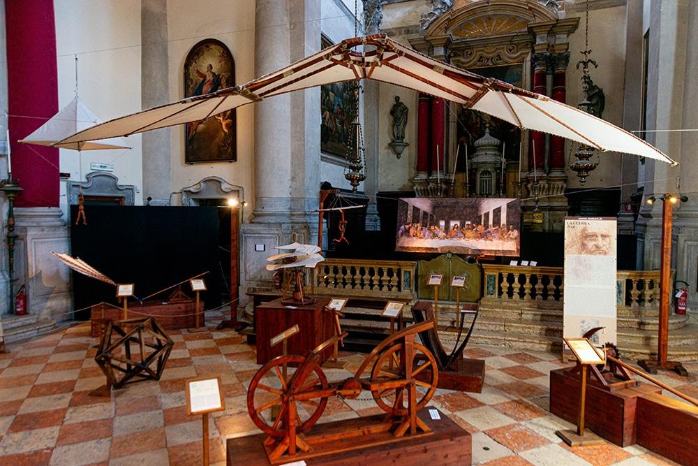 Intérieur d'une église catholique dans laquelle sont exposées des modèles de machines en bois inspirées des dessins de Leonardo da Vinci