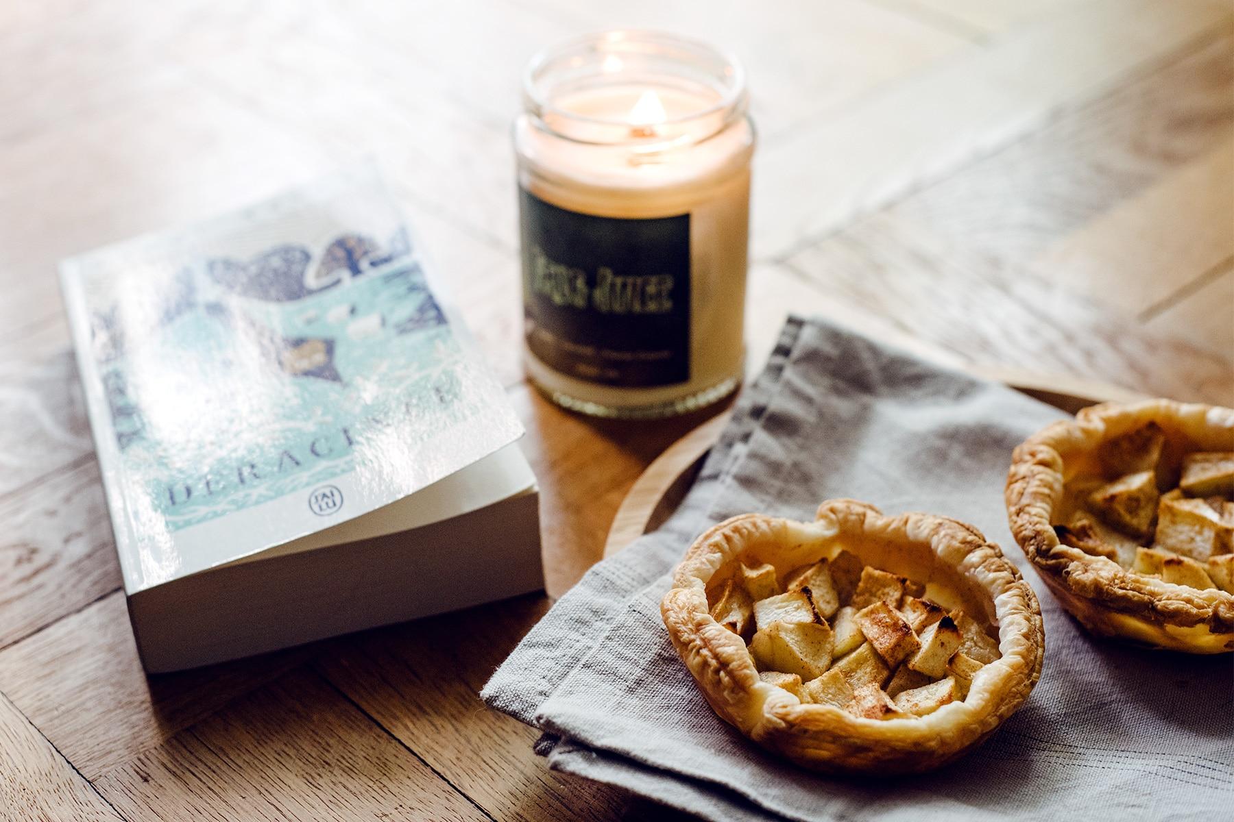 Ambiance automnale à la maison: tartelettes aux pommes, bougie parfumée et roman de sorcières