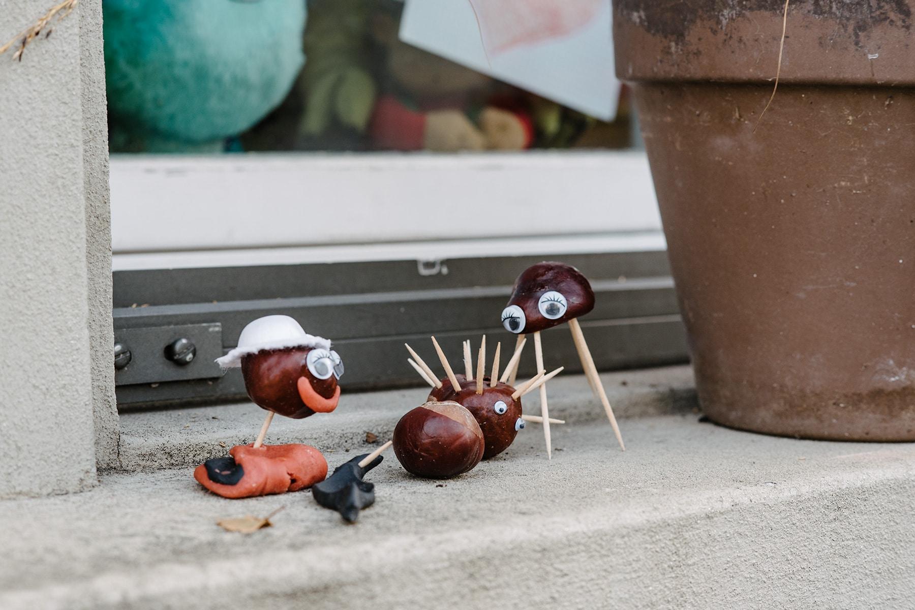 Petits personnages bricolés avec des marrons et de cure-dents, disposés sur le rebord d'une fenêtre