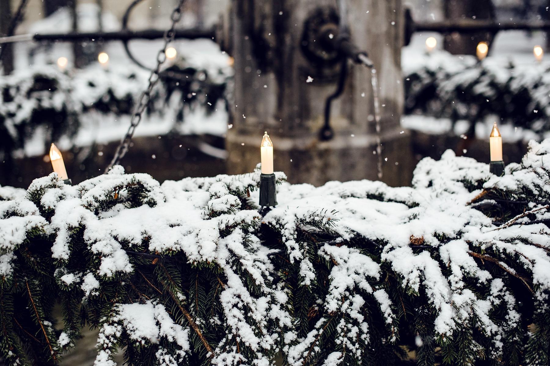 Fontaine décorée de branches de sapin et de bougies, saupoudrée de neige fraîche