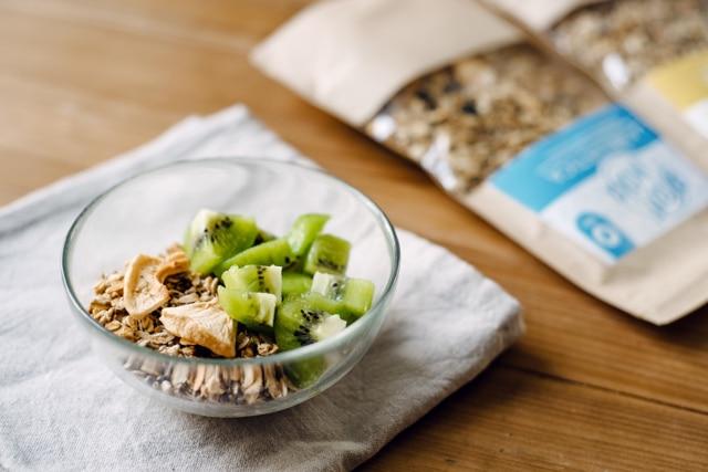 Bol de granola artisanal accompagné de yaourt végétal et d'un kiwi