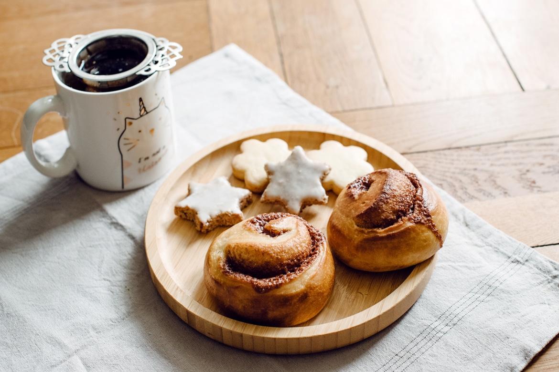 Brioches roulées à la cannelle, biscuits de Noël et tasse de thé hivernal